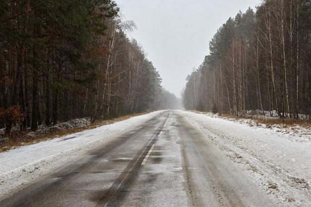 Lege rechte snelweg in de sneeuw door een dennenbos