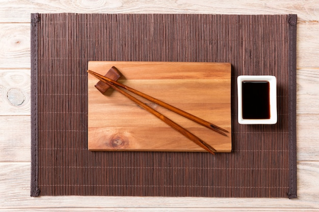 Lege rechthoekige houten plaat voor sushi met saus en eetstokjes op hout