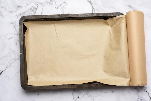Lege rechthoekige metalen bakplaat en rol bruin perkamentpapier op wit