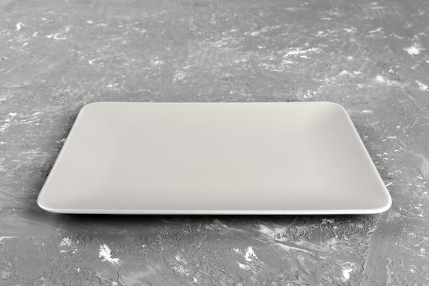 Lege rechthoekige plaat op grijze tafel