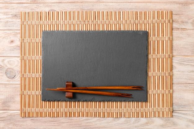 Lege rechthoekige zwarte leiplaat met eetstokjes voor sushi op hout
