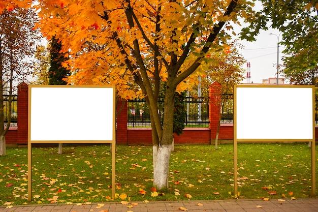Lege reclameborden met kopieerruimte tegen fel herfstgebladerte leeg wit uithangbord