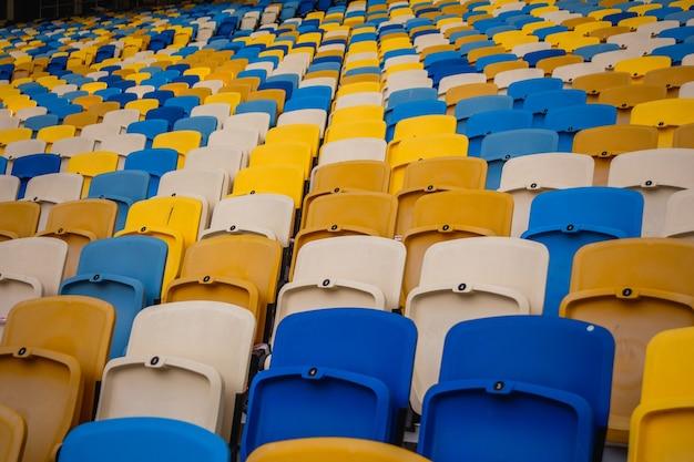 Lege rijen stoelen in een olympisch voetbalstadion met gele en blauwe banken