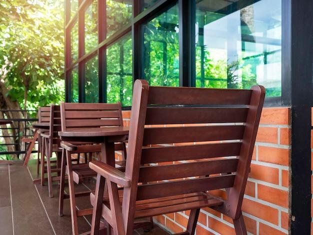 Lege rode gezellige houten stoelen en ronde houten salontafel bij het glazen raam en bakstenen muur met groene tuin in het café, zomer.