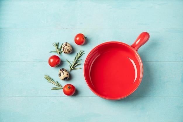 Lege rode pan. ingrediënten voor het koken: eieren, tomaat, rozemarijn.