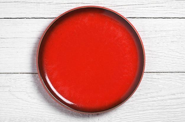 Lege rode plaat op witte houten tafel, bovenaanzicht