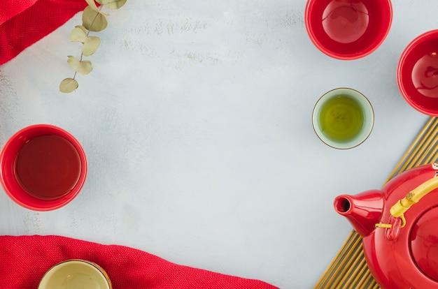 Lege rode theekoppen en theepot op witte achtergrond