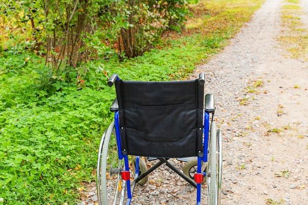 Lege rolstoel die zich op weg in het ziekenhuispark bevindt