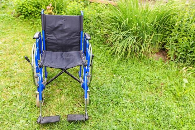 Lege rolstoel staande op gras in ziekenhuispark ongeldige stoel voor mensen met een handicap buiten geparkeerd in de natuur Premium Foto