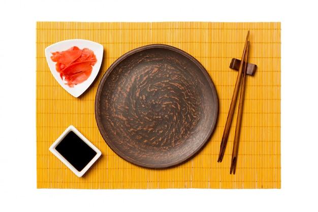 Lege ronde bruine plaat met stokjes voor sushi, gember en sojasaus op gele bamboemat