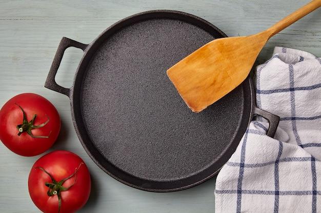 Lege ronde gietijzeren pan, houten spatel, theedoek en tomaten op een blauwe houten tafel. sjabloon voor het opmaken van een gerecht