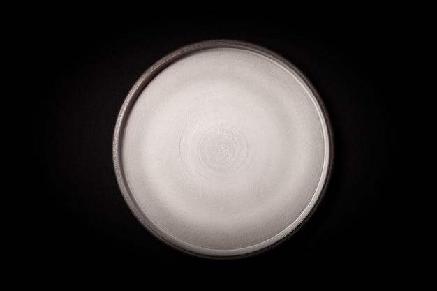 Lege ronde grijze keramische plaat op zwarte achtergrond