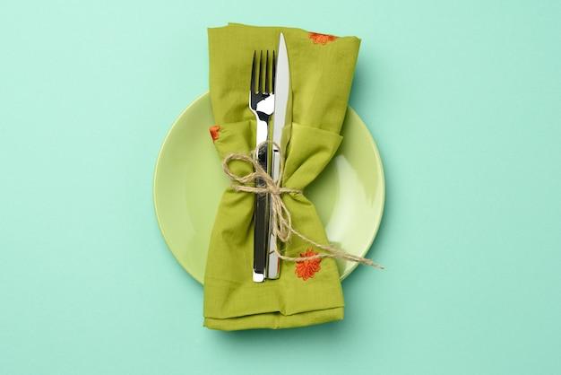 Lege ronde groene ceramische plaat en metaalvork en mes