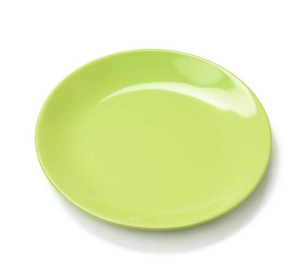 Lege ronde groene plaat voor hoofdgerechten geïsoleerd op een witte achtergrond, bovenaanzicht