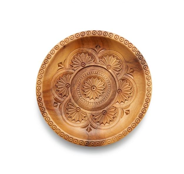 Lege ronde houten plaat met gesneden ornament dat op witte achtergrond wordt geïsoleerd