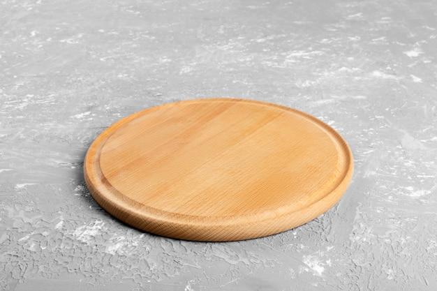Lege ronde houten plaat op getextureerde tafel. houten plaat voor eten of groente serveren aan klanten