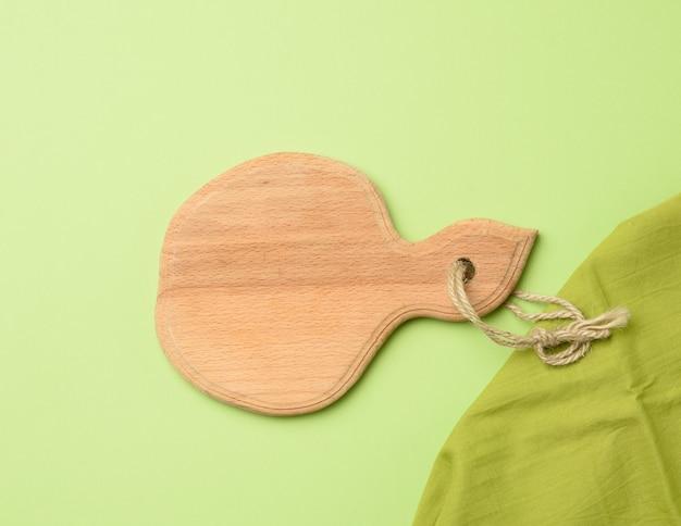 Lege ronde houten plank op een groene achtergrond, bovenaanzicht