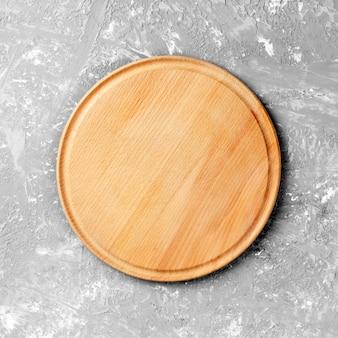 Lege ronde houten schotel op tafel