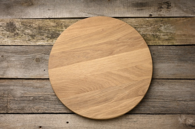 Lege ronde houten snijplank op houten oppervlak, pizzabord, bovenaanzicht