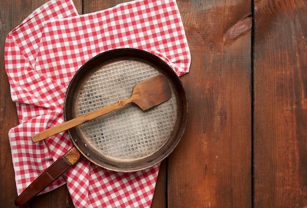 Lege ronde koekenpan met handvat op bruin houten tafel, bovenaanzicht
