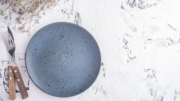 Lege ronde plaat geserveerd met fortk en mes.