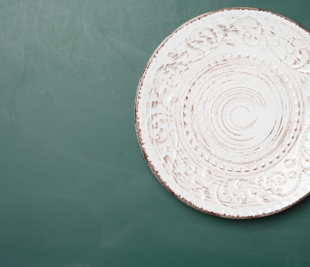 Lege ronde plaat voor hoofdgerechten op een groene tafel, bovenaanzicht
