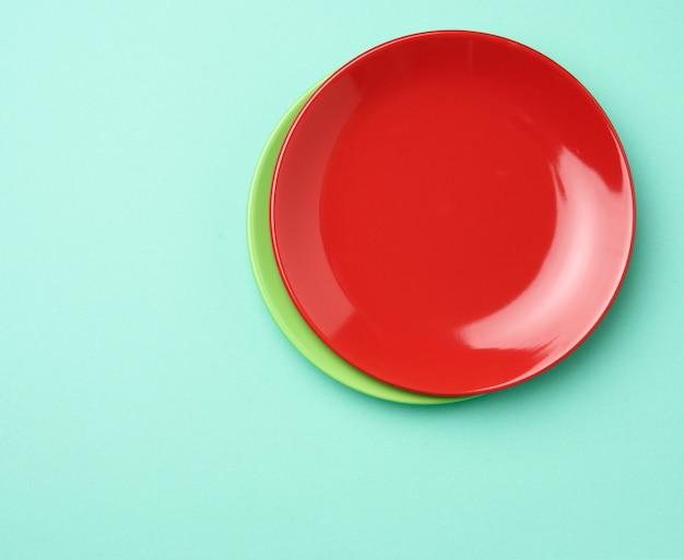 Lege ronde rode plaat voor hoofdgerechten op een groene achtergrond, bovenaanzicht, kopie ruimte