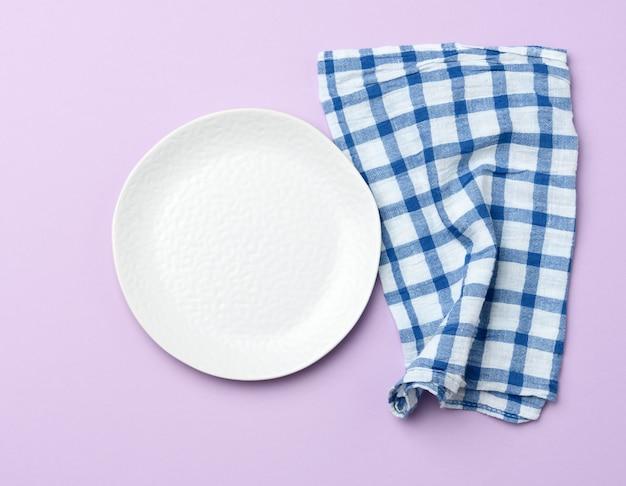 Lege ronde witte keramische plaat en blauwe servet paarse achtergrond