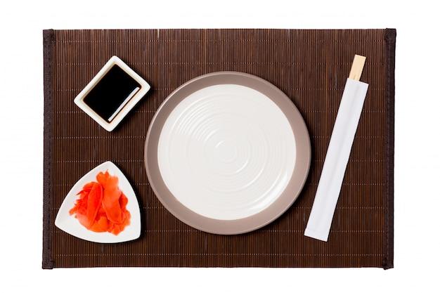 Lege ronde witte plaat met eetstokjes voor sushi