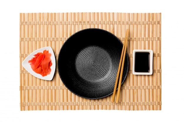 Lege ronde zwarte plaat met eetstokjes voor sushi en sojasaus, gember op de gele achtergrond van de bamboemat