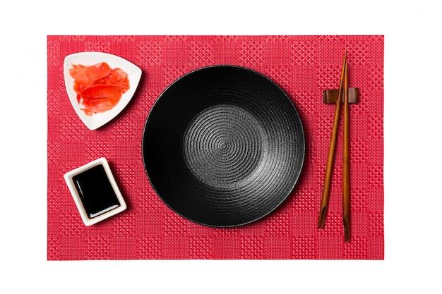 Lege ronde zwarte plaat met stokjes voor sushi en sojasaus, gember op rode mat sushi