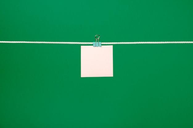 Lege roze papieren notitie over waslijn