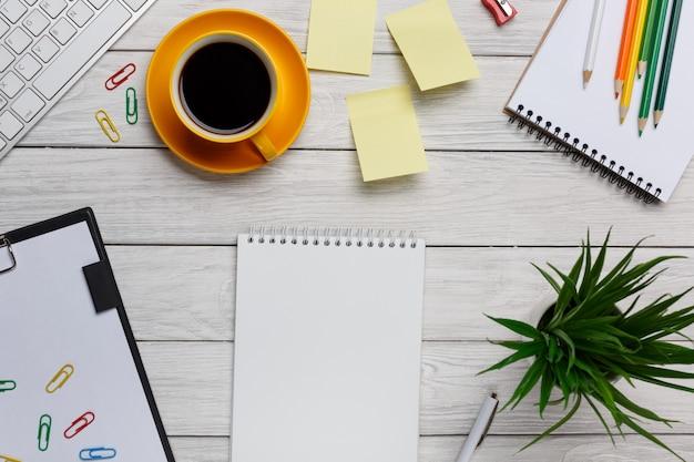 Lege ruimte naast kantoorapparatuur zoals modern wit computertoetsenbord, muis, notitieblok, notitie en plant.