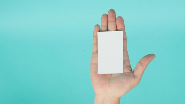 Lege ruimte voor tekst. mannelijke hand met witte lege kaart geïsoleerd op mintgroen of tiffany blue achtergrond.