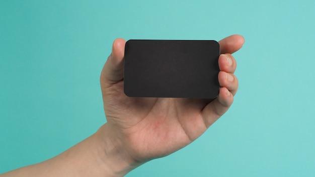 Lege ruimte voor tekst. mannelijke hand met zwarte lege kaart geïsoleerd op mintgroen of tiffany blue achtergrond.