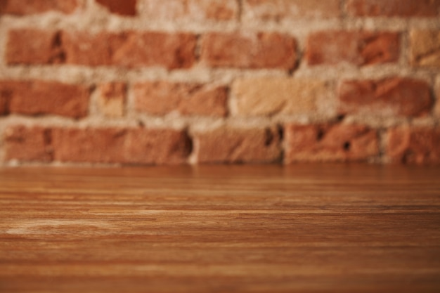 Lege rustieke bruine houten tafel met bakstenen muur achter, achtergrond voor stilleven en andere composities
