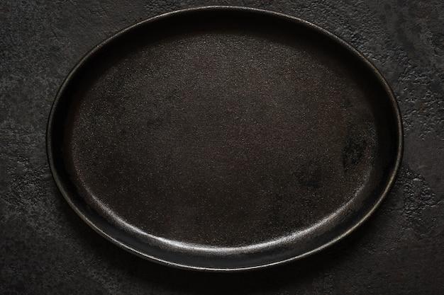 Lege rustieke zwarte gietijzeren plaat op donkere betonnen achtergrond. bovenaanzicht met kopie ruimte.