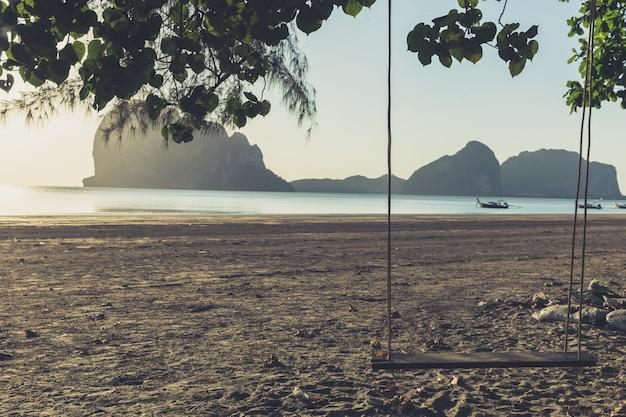Lege schommel op het strand vintage kleurtoon met zonsondergang