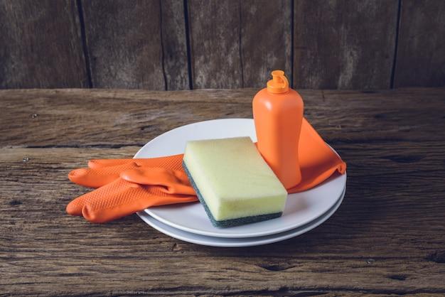 Lege schone borden en beker met afwasmiddel, sponzen, rubberen handschoenen