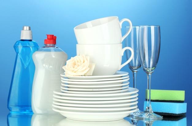 Lege schone borden, glazen en kopjes met afwasmiddel en sponzen op blauwe achtergrond