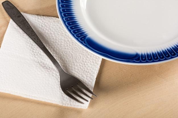Lege schotel en vork op een servet