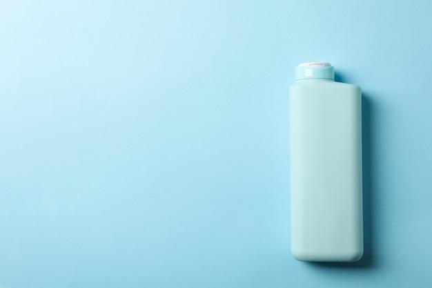 Lege shampoofles op blauwe achtergrond, ruimte voor tekst