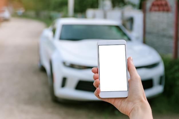 Lege smartphone in vrouwenhand, op de achtergrond een witte auto