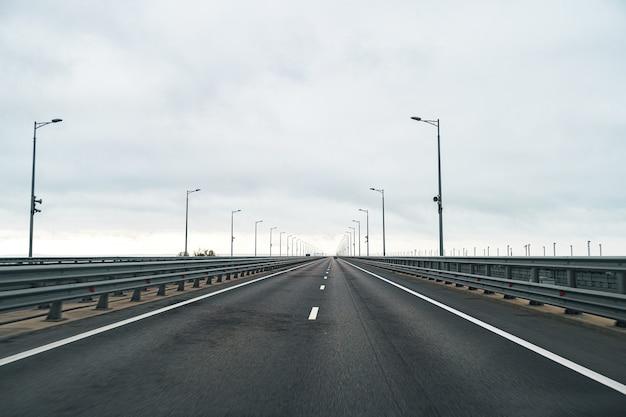 Lege snelweg met asfaltweg en bewolkte hemel