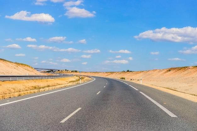 Lege snelweg tegen een blauwe hemel met wolken bij zonnig weer