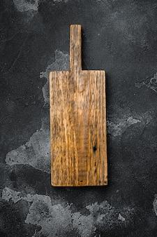 Lege snijplankenset, op zwarte donkere stenen tafelachtergrond, bovenaanzicht plat gelegd, met kopieerruimte voor tekst of uw product