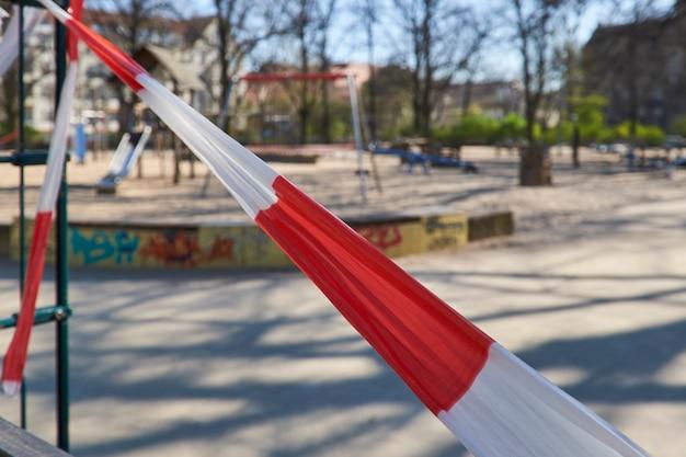 Lege speeltuin zonder kinderen, gesloten voor kinderen en ouders. knip af met gestreepte rood-witte waarschuwingstape.
