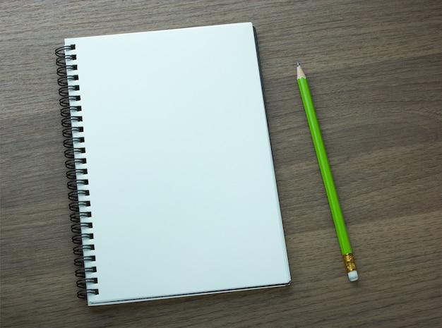 Lege spiraal notitieboekje en potlood op donkere houten achtergrond