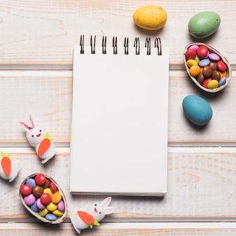 Lege spiraalvormige blocnote met kleurrijke gemmen; paas eieren; witte konijntjes op houten bureau