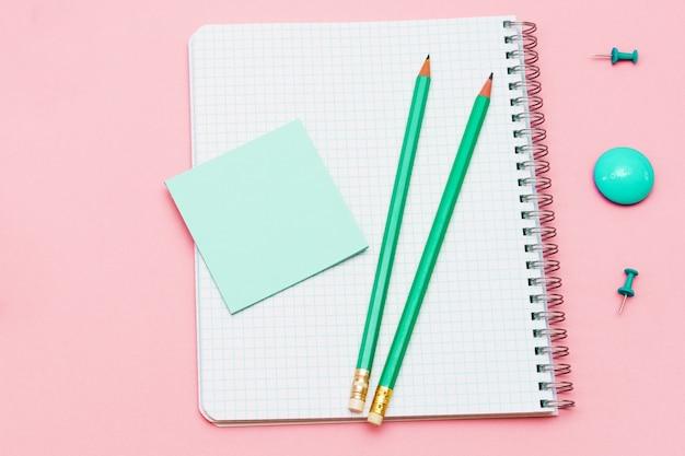 Lege spiraalvormige blocnote met witte pagina en houten potlood op roze oppervlak